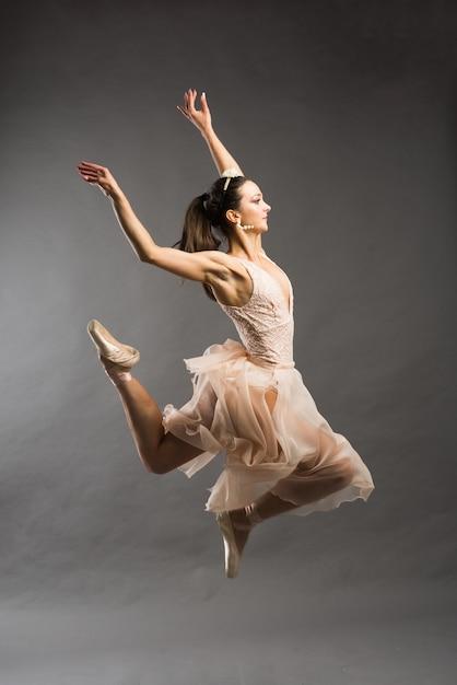 Jonge mooie balletdanser in beige zwembroek poseren op pointes op lichtgrijze studio achtergrond Premium Foto