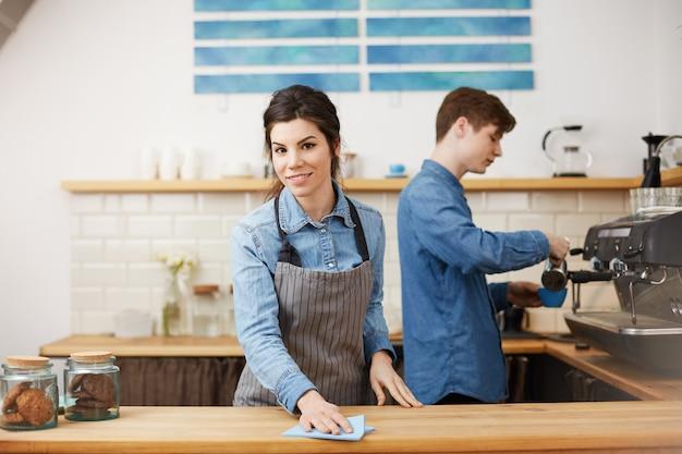 Jonge mooie barista's in uniform werken aan toog. Gratis Foto