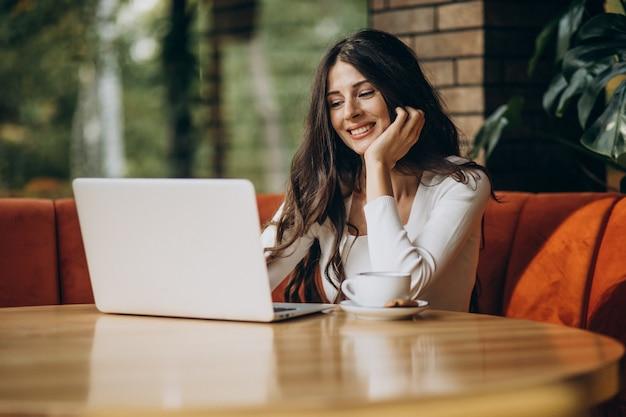 Jonge mooie bedrijfsvrouw die aan computer in een koffie werkt Gratis Foto