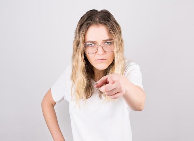 Jonge mooie blanke vrouw die ontevreden en gefrustreerd naar de camera wijst Premium Foto