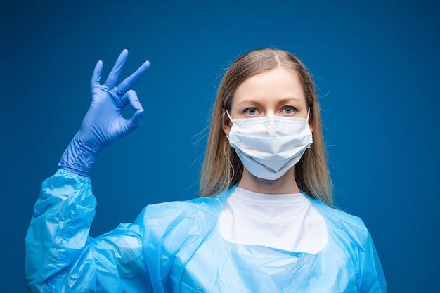 Jonge mooie blanke vrouw in blauwe medische jurk en met wit medisch masker op haar gezicht kijkt op de camera en toont ok Gratis Foto