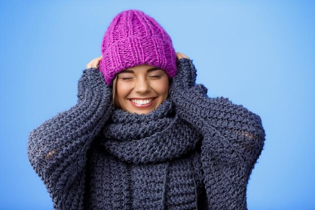 Jonge mooie blonde vrouw in gebreide muts en trui lachend op blauw. Gratis Foto