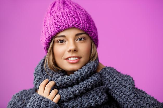 Jonge mooie blonde vrouw in gebreide muts en trui lachend op violet. Gratis Foto