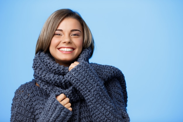 Jonge mooie blonde vrouw in hoed en trui lachend op blauw. Gratis Foto
