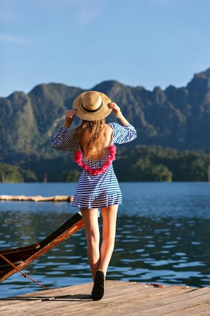 Jonge mooie blonde vrouw met lange haren, vintage hoed en heldere sexy trendy jurk dragen kijkt naar de bergen en het meer, laat haar hand zien, geweldige zomeravonturen. Gratis Foto