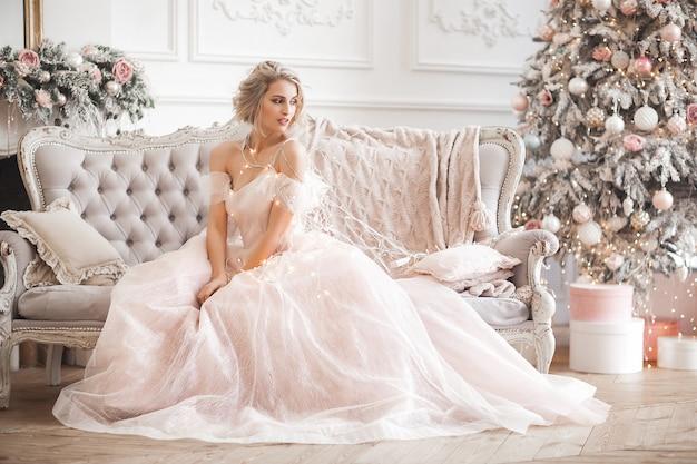 Jonge mooie blonde vrouw op de volledige hoogte van de kerstmisscène. aantrekkelijke dame in prachtige roze jurk. Premium Foto