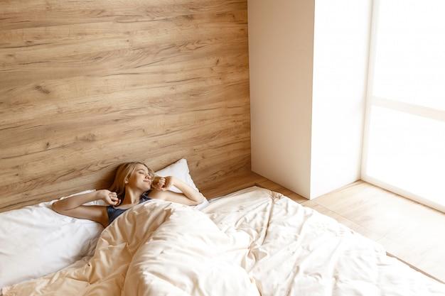 Jonge mooie blondevrouw die in bed in ochtend liggen. zij wordt wakker. model stretch handen omhoog. slaperige schoonheid. alleen in de kamer. daglicht. Premium Foto