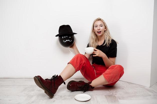 Jonge mooie blondevrouw die zwarte ballon in hoedenzitting houden op vloer het drinken koffie over witte muur Gratis Foto