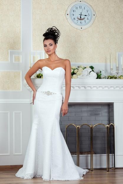 Jonge mooie bruid permanent in de buurt van open haard in luxe trouwjurk Premium Foto