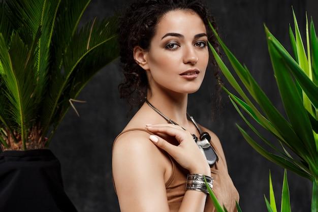 Jonge mooie brunette meisje in tropische planten over grijze muur Gratis Foto