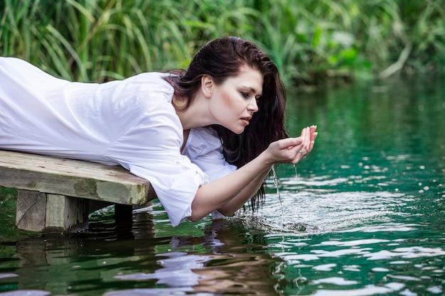 Jonge mooie brunette vrouw geniet van het meer met turkoois helder water Premium Foto