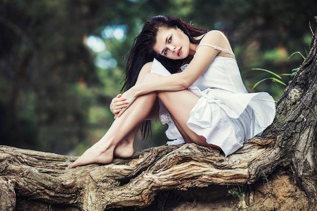 Jonge mooie brunette vrouw genieten van zitten en rusten in het bos Premium Foto