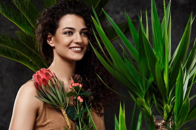Jonge mooie brunette vrouw in tropische planten over grijze ondergrond Gratis Foto
