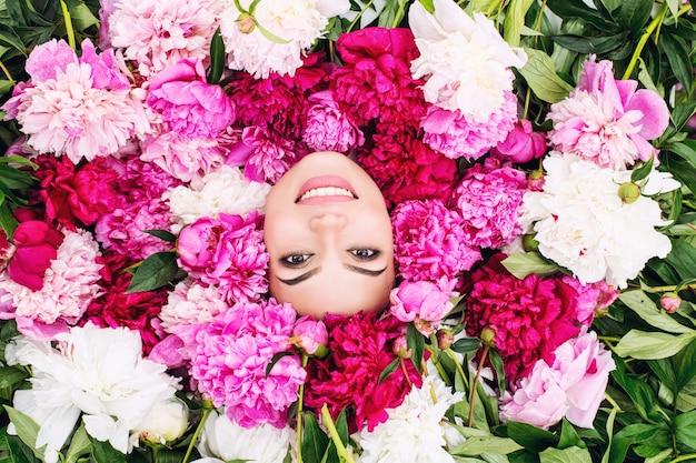 Jonge mooie brunette vrouw model met mooie make-up en lang haar in roze kleuren - pioenrozen Premium Foto