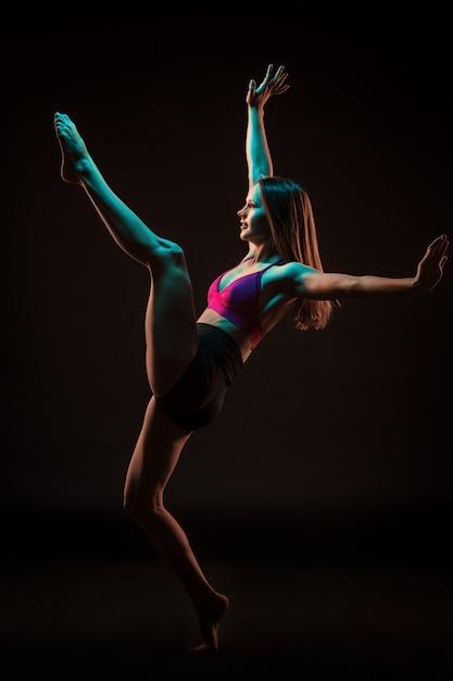 Jonge mooie danser dansen op zwarte muur Gratis Foto