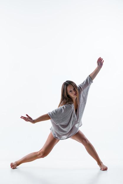 Jonge mooie danser in beige jurk dansen op wit Gratis Foto