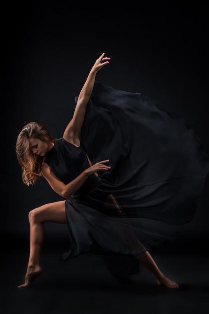 Jonge mooie danser in beige jurk dansen op zwart Gratis Foto
