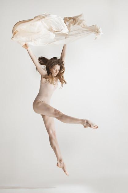 Jonge mooie danser in beige zwembroek dansen op grijs Gratis Foto