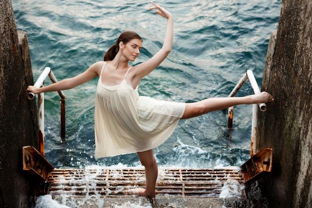 Jonge mooie en ballerina die, zeedijk buiten dansen stellen Gratis Foto