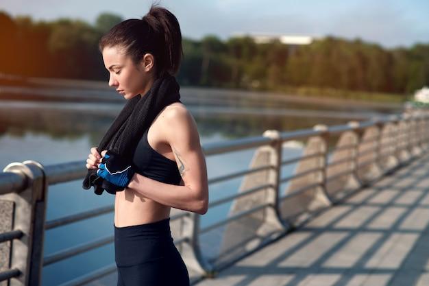 Jonge mooie en sterke vrouw die na een actieve training in het de zomerpark rusten. sport concept. gezonde levensstijl Premium Foto