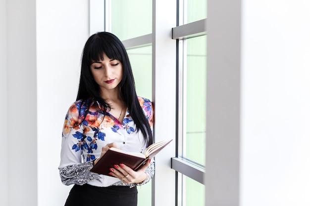 Jonge mooie ernstige vrouw permanent in de buurt van het venster, schrijven in notitieblok, op zoek naar de laptop. Premium Foto