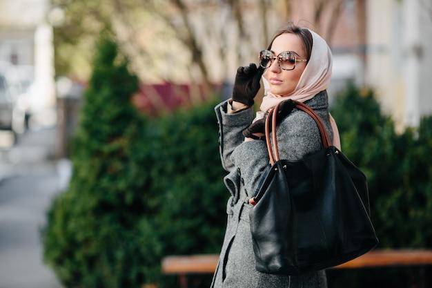Jonge mooie gelukkige vrouw in een jas die zich voordeed in het park Gratis Foto