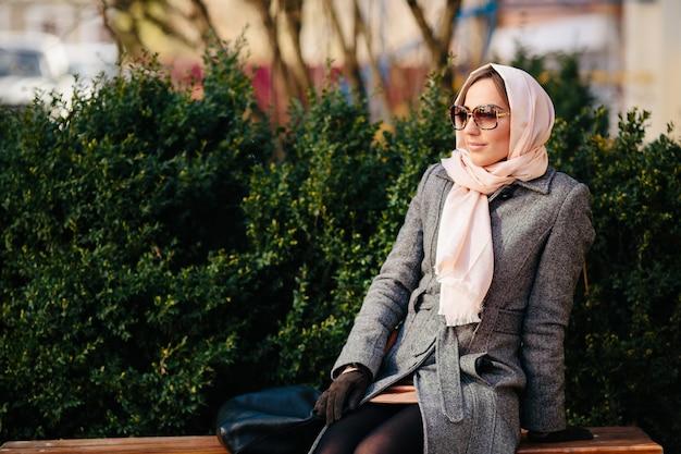 Jonge mooie gelukkige vrouw in een jas zittend op een bankje in het park Gratis Foto