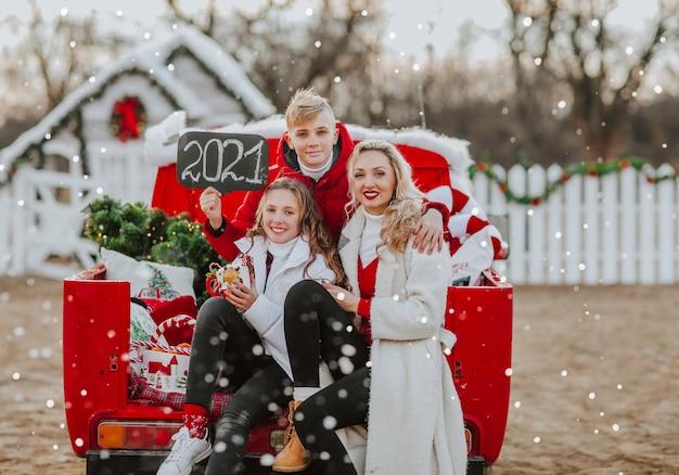 Jonge mooie gezin van drie in rode en witte winterkleren poseren in rode open retro auto met kerstboom en naamplaatje met 2021-teken onder het sneeuwt. Premium Foto