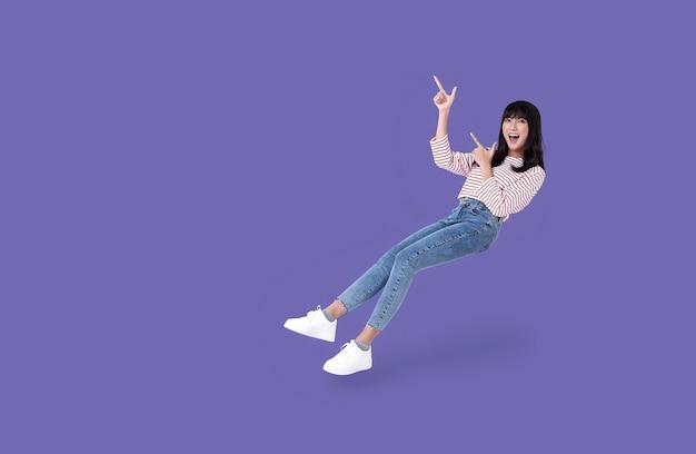 Jonge mooie glimlachende aziatische meisjeshand die omhoog wijst om ruimte op paars te kopiëren. Premium Foto
