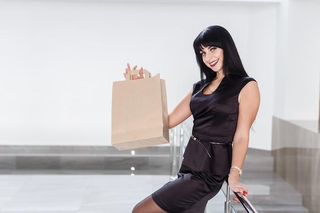 Jonge mooie glimlachende brunette vrouw met papieren boodschappentas, lopen op een winkelcentrum. Premium Foto
