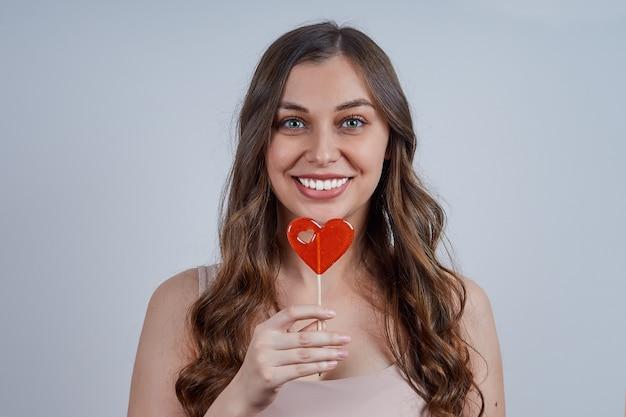 Jonge mooie glimlachende vrouw met rood hartsuikergoed. Premium Foto