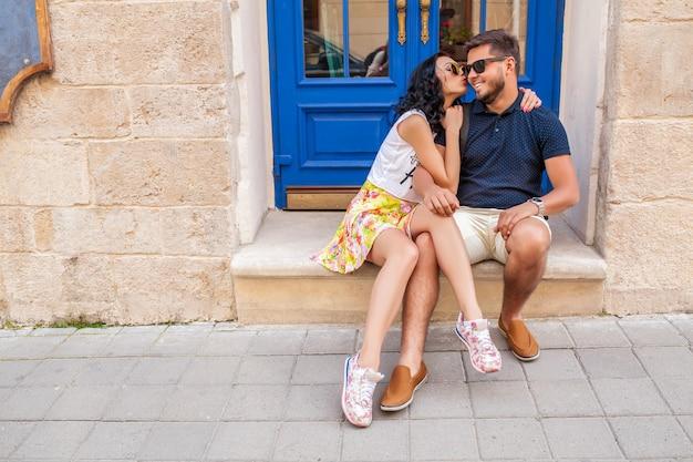 Jonge mooie hipster paar verliefd zittend op oude stad straat Gratis Foto