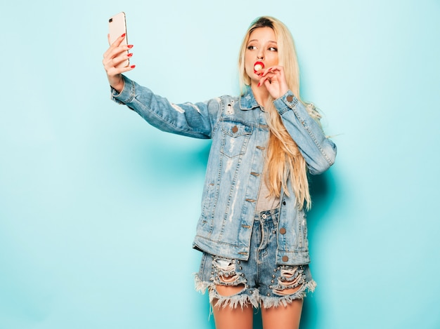 Jonge mooie hipster slecht meisje in trendy jeans zomerkleding en oorbel in haar neus. positief model dat rond suikersuikergoed likt neemt selfie foto Gratis Foto