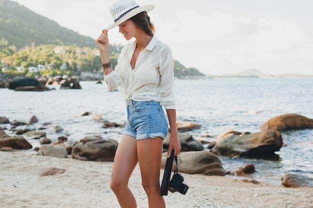 Jonge mooie hipster vrouw op zomervakantie in azië, ontspannen op tropisch strand, digitale fotocamera, casual boho-stijl, zee landschap, slank gebruind lichaam, alleen reizen Gratis Foto
