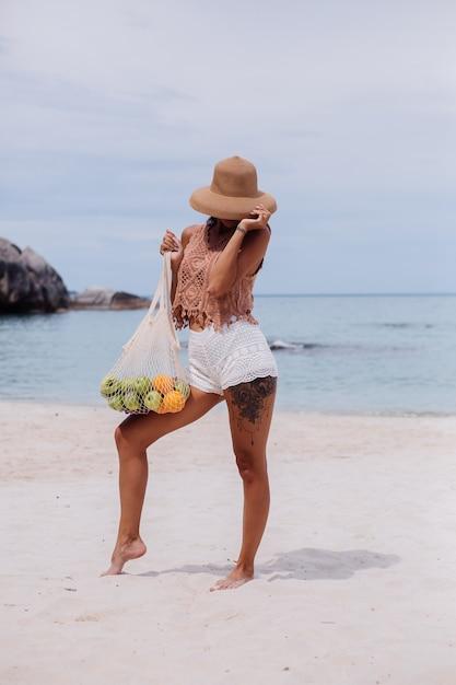 Jonge mooie kaukasische gelooide fit vrouw in gebreide kleding op tropisch strand dragen strooien hoed bedrijf ecologie herbruikbare tekenreeks tas vol fruit apple oranje druiven Gratis Foto