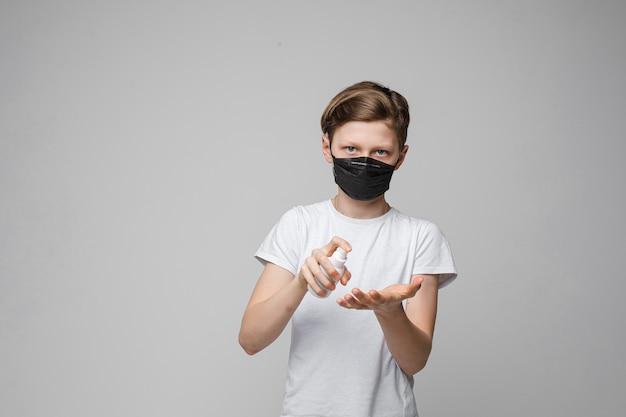 Jonge mooie kaukasische tiener in wit t-shirt, zwarte spijkerbroek staat met zwarte medische masker desinfecteert zijn handen met anticepticum Gratis Foto