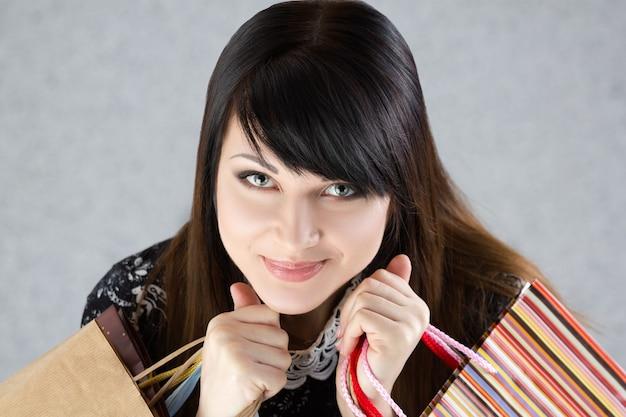 Jonge mooie lachende vrouw met papieren zakken met aankopen. verkoop en winkelconcept Premium Foto
