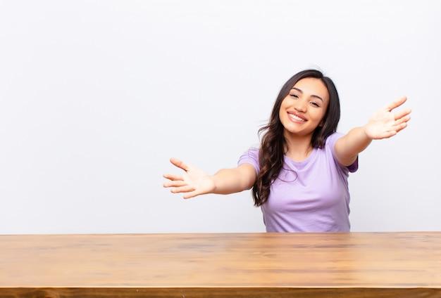 Jonge, mooie latijnse vrouw die vrolijk glimlacht en een warme, vriendelijke, liefdevolle welkomstomhelzing geeft, zich gelukkig en schattig voelt tegen een vlakke muur Premium Foto