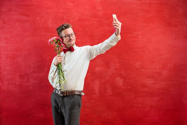 Jonge mooie man met bloemen en telefoon Gratis Foto