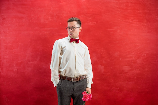 Jonge mooie man met bloemen op rode studio achtergrond Gratis Foto