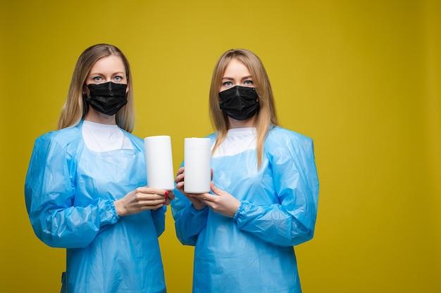 Jonge mooie meisjes in een wegwerp medische jassen en met een masker op hun gezicht houdt natte antibacteriële doekjes, portret geïsoleerd op gele achtergrond Gratis Foto