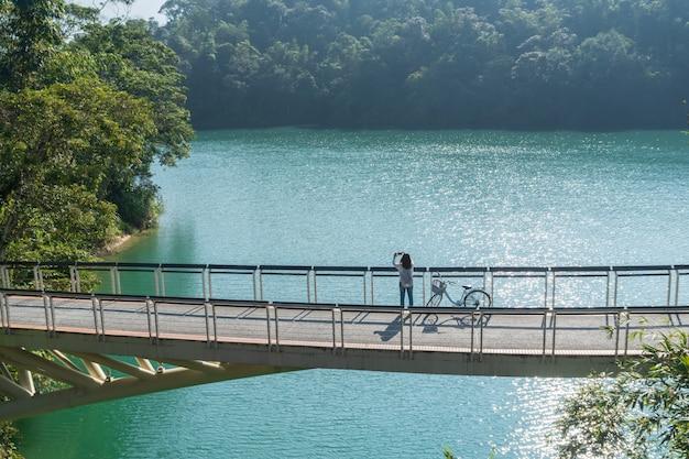 Jonge mooie meisjestribune dichtbij een fiets terwijl neem een foto van het mening vooraan op fietssleep bij het meer in de ochtend. actieve mensen. buitenshuis Premium Foto