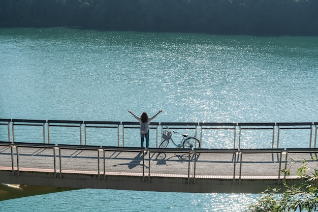 Jonge mooie meisjestribune dichtbij een fiets terwijl rust haar handen op fietssleep bij het meer in de ochtend. actieve mensen. buitenshuis Premium Foto