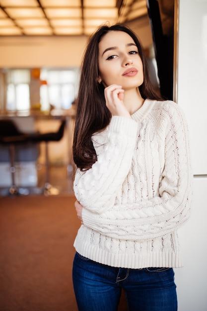 Jonge mooie model met grote ogen rode lippen en lang bruin haar in spijkerbroek blijven in de kamer bij haar thuis Gratis Foto