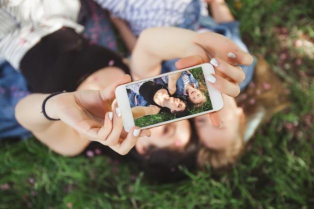 Jonge mooie moeder en haar dochtertje selfie maken op mobiele telefoon. moeder en haar baby meisje buitenshuis plezier in het park. meisjes maken foto op mobiele telefoon en glimlachen Premium Foto
