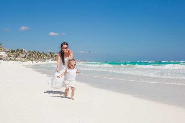 Jonge mooie moeder en haar schattige kleine dochter die langs de zee loopt Premium Foto