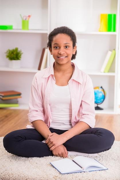 Jonge mooie mulat schoolmeisje zittend op het tapijt. Premium Foto