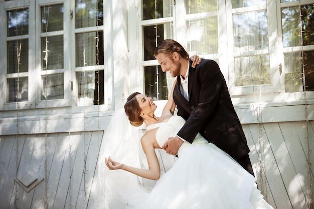 Jonge mooie opgedirkte jonggehuwden glimlachen, buitenshuis dansen. Gratis Foto