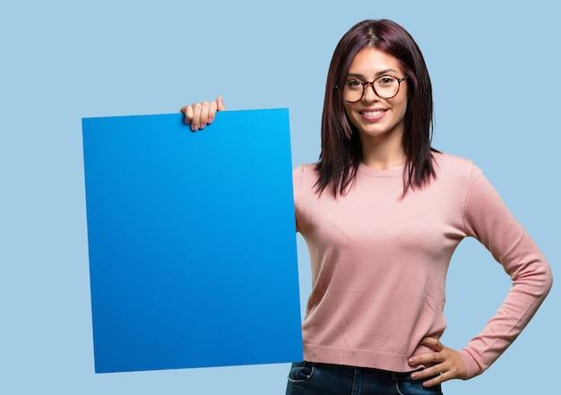 Jonge mooie opgewekte en gemotiveerde vrouw, die een lege affiche toont waar u een bericht, communicatie concept kunt tonen Premium Foto