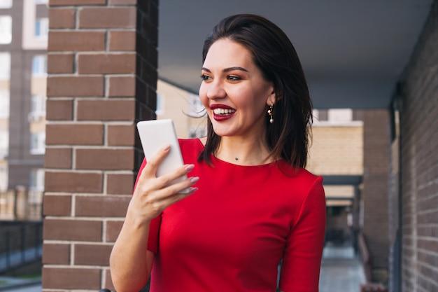 Jonge mooie opgewonden gelukkige vrouw met rode lippenstift en buiten het dragen van rode kleding die mobiele telefoon houdt Premium Foto